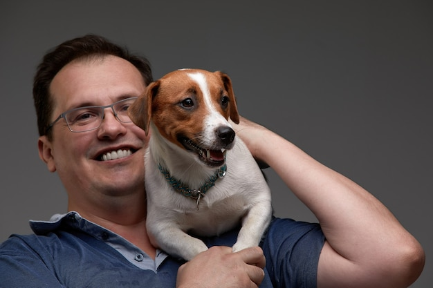 카메라를 보고 웃으면서 그의 손에 강아지를 들고 캐주얼 젊은 남자. 회색 배경에.