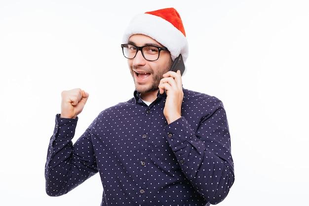 電話で話し、応援するサンタの帽子をかぶったカジュアルな若い男