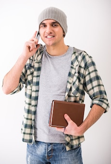 Casual young man is talking by phone and holding books.