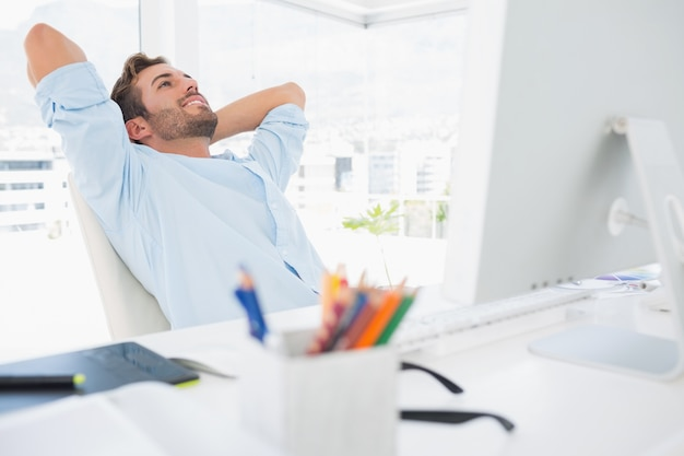 Casual young man resting with hands behind head in office