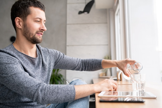 カジュアルな若い男がカフェの窓際に座って、短い休憩中にボトルからグラスに水を注ぐ