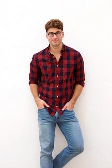 Casual young man with glasses standing and smiling