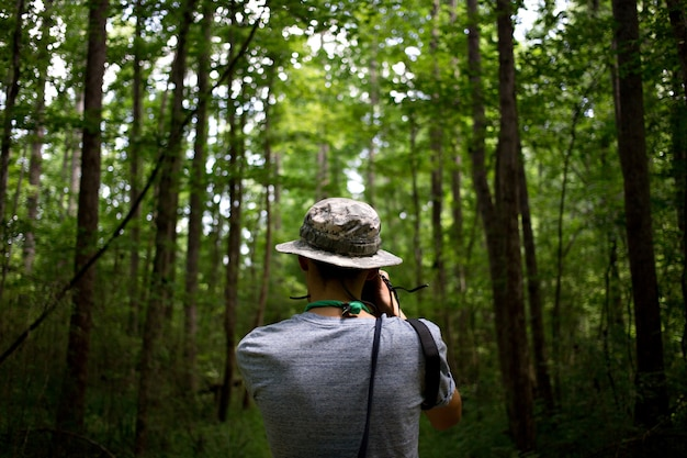 Casual young man with green cap in a jungle park makes photos of nature