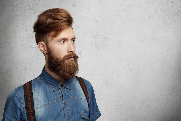 Casual young man with stylish fuzzy beard dressed in denim shirt and suspenders looking ahead of him at blank wall