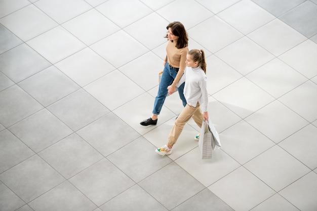 カジュアルな若い女性と彼女の娘が買い物をしながら現代的なモールに沿って動く紙袋