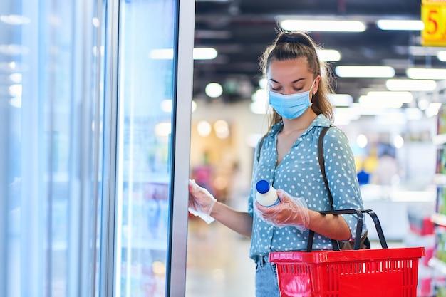 買い物かごを持つ医療用防護マスクのカジュアルな若い女性バイヤーは、食料品店の冷凍庫から乳製品を選択します