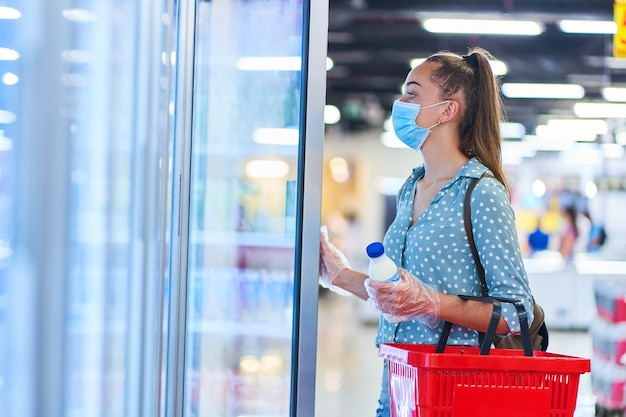 買い物かごを持つ医療用防護マスクのカジュアルな若い女性バイヤーは食料品店の冷凍庫から乳製品を選択します