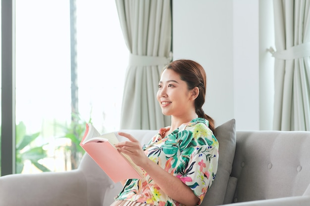 自宅のソファで童話を読んでカジュアルな若い女性