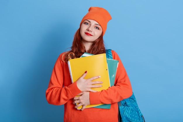 分離されたバッグバックパックと紙フォルダーを持つカジュアルな若い女性の学生