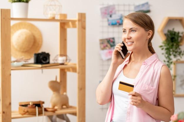 スマートフォンとオンラインショップのコンサルタントに話しながら電話で注文するプラスチック製のカードを持つカジュアルな若い女性