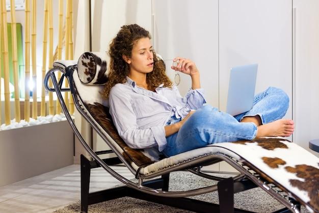 Повседневная молодая женщина, работающая дома на портативном компьютере, расслабляется в кресле с откидной спинкой во внутреннем дворике во время работы на дому