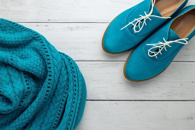 Пары женского низкого ботинка и голубого пуловера на светлой деревянной предпосылке. плоская планировка, современные тенденции модной одежды. вид сверху. концепция стиля casual.