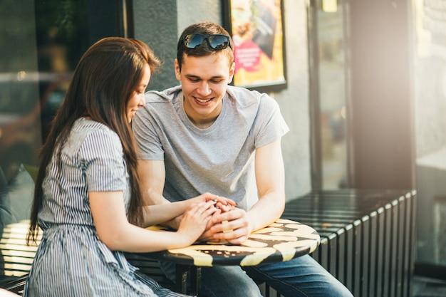 Счастливая молодая пара в любви подростков друзей, одетых в стиле casual, сидя вместе
