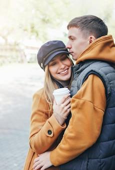 Счастливая молодая пара в любви подростков друзей, одетых в стиле casual, гуляя вместе по улице города в холодное время года