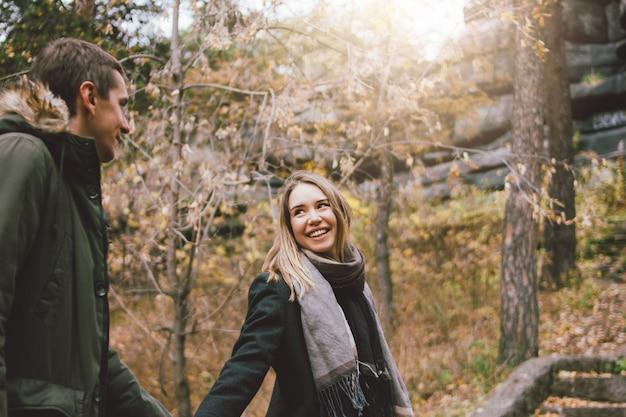 Счастливые молодые влюбленные друзья, одетые в стиле casual, гуляют вместе по лесу в холодное время года, путешествуют по семейным приключениям