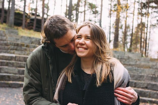 Молодая счастливая пара в любви друзей, одетых в стиле casual, гуляя вместе по осеннему парку