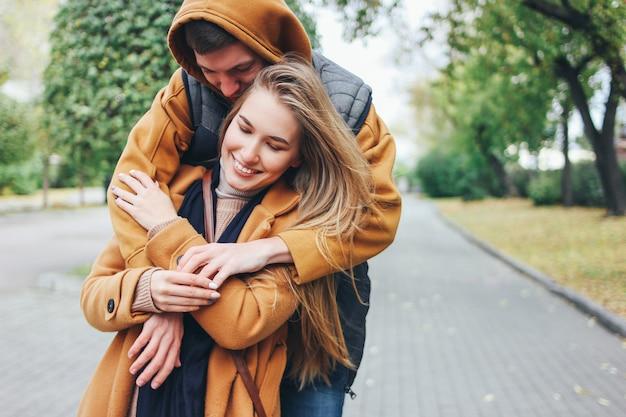 Счастливая молодая пара в любви подростков друзей, одетых в стиле casual, сидели на осенней городской улице