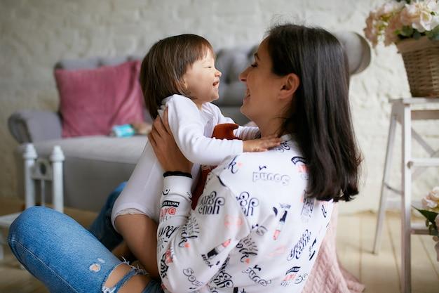 Маленькая девочка и ее мама, одетая в стиле casual, весело играют на полу
