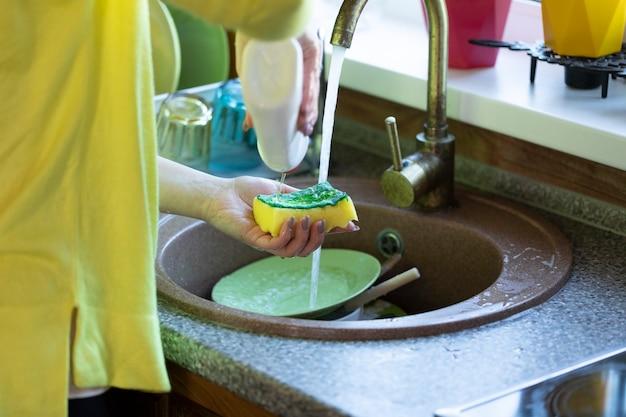 カジュアルな服装の女性がカントリーハウスのクローズアップで水の噴流の下で皿を洗う