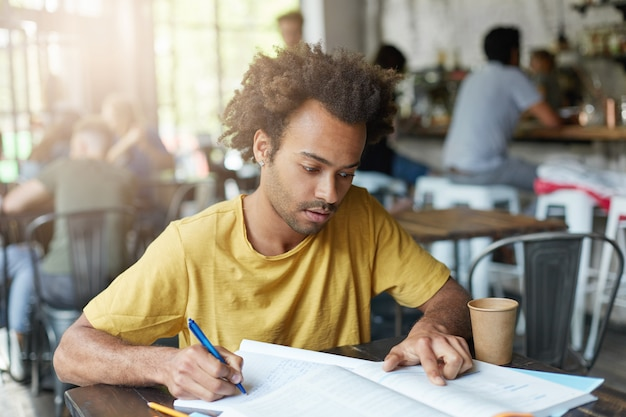Casually dressed young black male student with beard and curly hair having focused concentrated look as he reads information in textbook and making notes in copybook, preparing for lesson at college