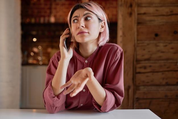 Небрежно одетая молодая женщина разговаривает по телефону, эмоционально жестикулируя в негодовании