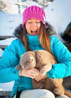 Кошка и молодая женщина, играя зимой