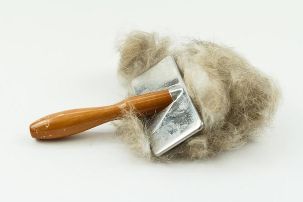 白で隔離された猫の毛の塊を持つ猫のブラシ、長い髪の猫のメンテナンス