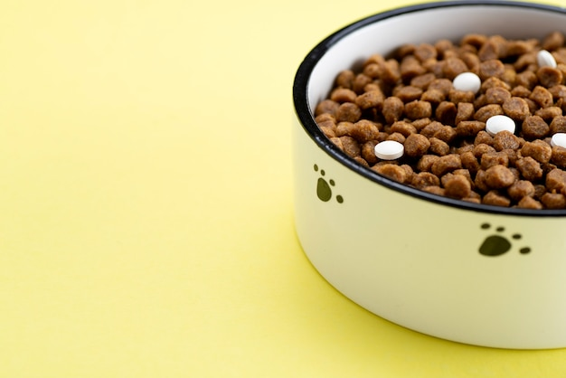 Cat food with white tablets in a bowl