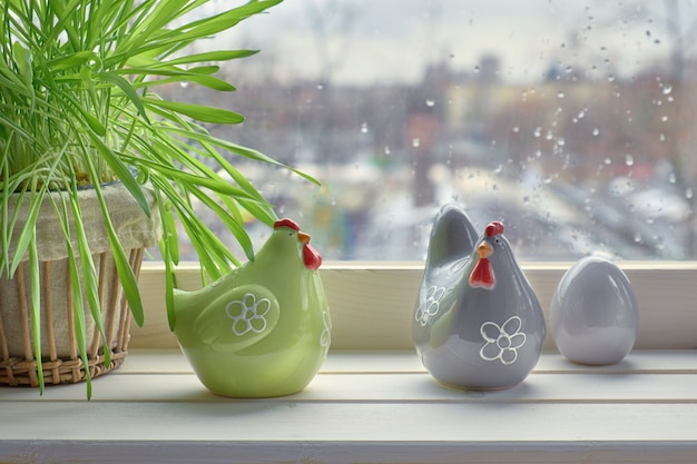 Cat grass and two ceramic hens with egg on a windowboard on a rainy day