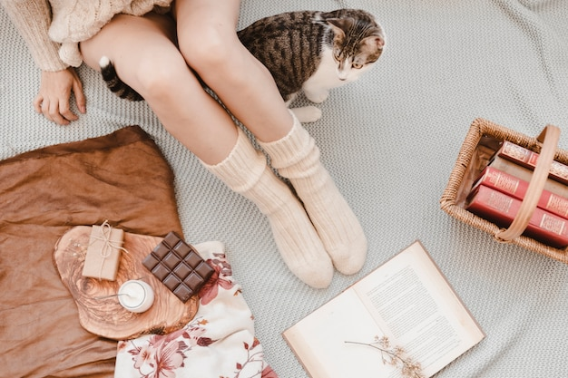 Cat walking near woman and books on bed
