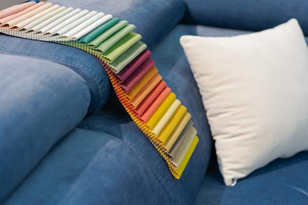 Catalog of multi-colored fabric samples on sofa
