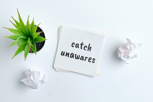 Catch unawares - english time idiom hand lettering on wooden blocks
