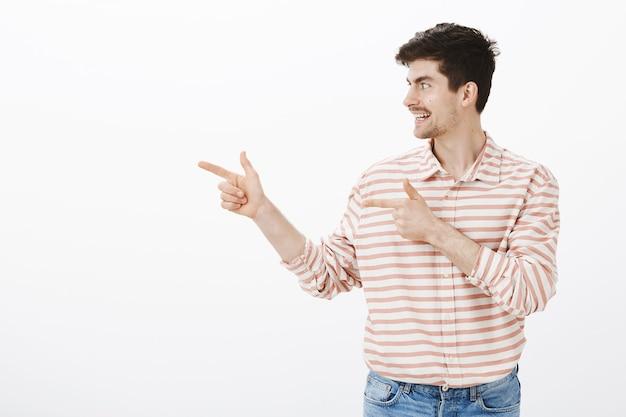 Ci vediamo dopo. colpo di amico maschio europeo positivo amichevole in camicia a strisce carina, che punta con le pistole e guarda a sinistra, salutando i compagni dopo aver lasciato la festa, in piedi sul muro grigio
