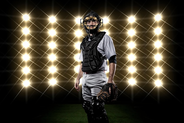 Catcher player in front of lights.