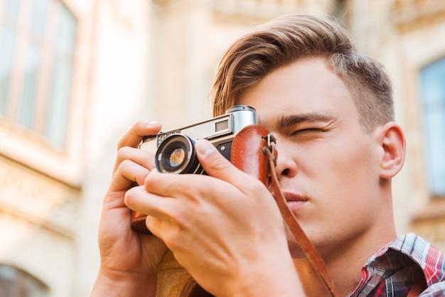 瞬間を捉える。屋外に立っている間彼のビンテージカメラで撮影しているハンサムな若い男のローアングルビュー