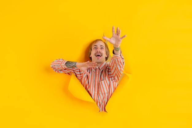 뭔가 잡기. 쾌활 한 백인 젊은 남자가 찢어진 된 노란 종이, 감정 및 표현 포즈.
