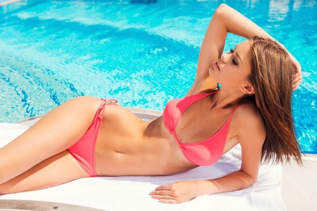 수영장에서 태양 광선을 잡기. 수영장 옆 갑판 의자에서 비키니를 입은 아름다운 젊은 여성