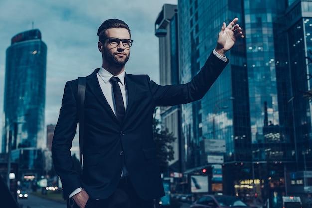 택시 잡기. 택시를 잡는 정장을 입은 자신감 있는 젊은 사업가의 야간 이미지