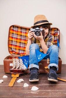 最高の瞬間をキャッチします。カメラを保持し、茶色の背景にスーツケースに座って笑っている帽子の小さな男の子