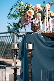 케이터링 이벤트 설정 꽃 양초 파란색 냅킨 및 식탁보 나무 테이블 야외