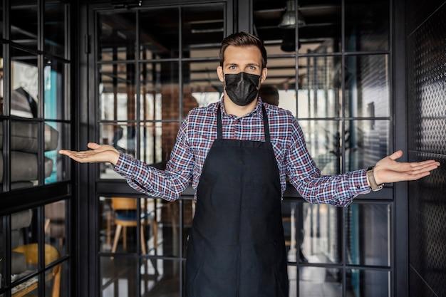 Общественное питание и вирус короны. официант в форме и в защитной маске стоит перед входом в ресторан и запрещает вход без защиты от вирусов. работник ресторана