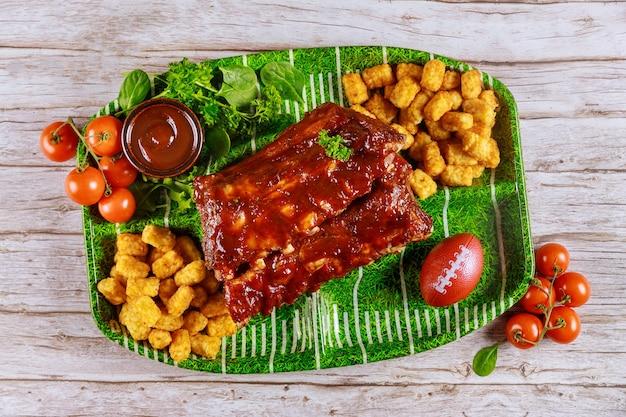 Питание для вечеринки по американскому футболу. ребрышки, картофель и салат.