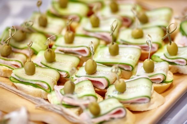 Питание канапе с оливками, огурцом и ветчиной