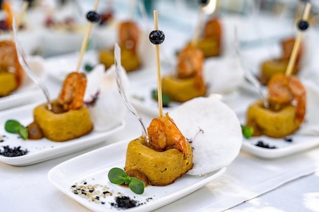 레스토랑에서 스낵과 음식을 제공하는 케이터링 서비스 배경. 흰색 테이블과 흰색 접시입니다. 다채로운 전채입니다.