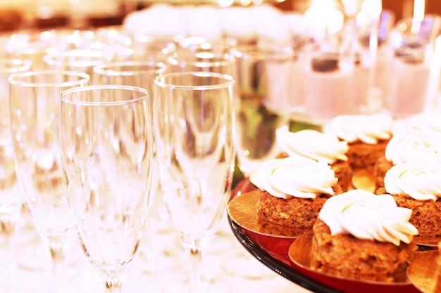 신선한 라즈베리와 견과류로 장식된 얇게 썬 초콜릿 케이크가 있는 케이터링 테이블.