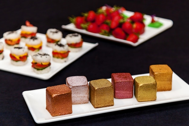 Catering, various delicious desserts on buffet plates. catering, assorted snacks on plates