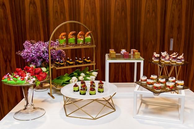 Питание, разнообразные вкусные закуски и десерты на фуршетных тарелках. кейтеринг, закуски ассорти