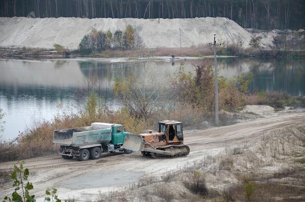 오픈 캐스트 채광 채석장에서 캐터필라 로더 및 덤프 트럭 작업