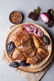 赤玉ねぎとバジルの丸いプレートにローストした魚を乗せたナマズのケバブシャシリク