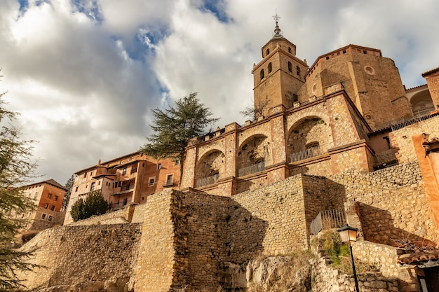 Cathedral of the city elevated over the blue sky with clouds. ancient construction with stone walls and medieval architecture. albarracã­n teruel spain. aragã³n.